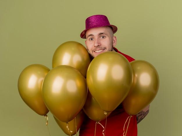 Ragazzo sorridente bello partito slavo che indossa il cappello del partito in piedi dietro i palloncini che guarda l'obbiettivo isolato su sfondo verde oliva