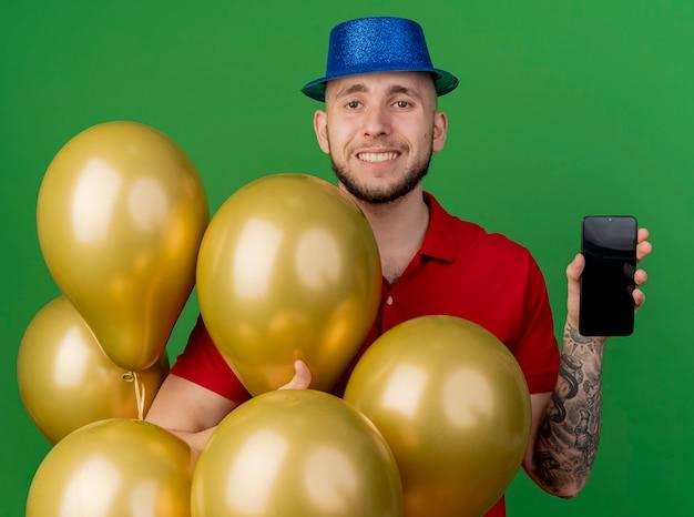 緑の背景に分離されたカメラを見ている携帯電話を示す風船の後ろに立っているパーティーハットを身に着けている若いハンサムなスラブ党の男を笑顔