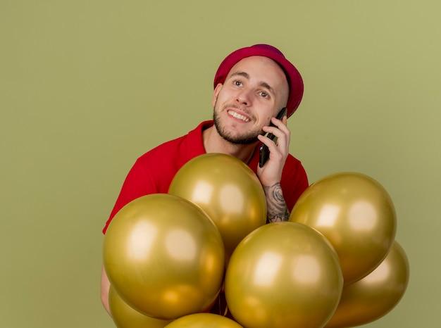 コピースペースでオリーブグリーンの背景に分離された側を見て電話で話している風船の後ろに立っているパーティー帽子をかぶって若いハンサムなスラブ党の男を笑顔
