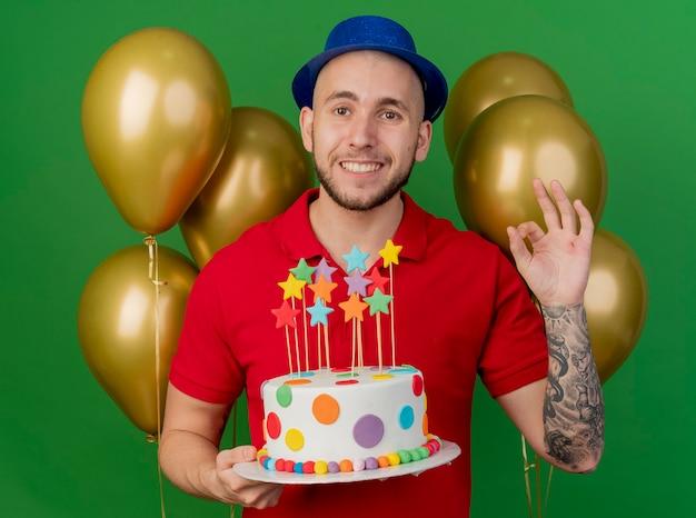 녹색 배경에 고립 된 확인 서명을 하 고 카메라를보고 생일 케이크를 들고 풍선 앞에 서있는 파티 모자를 쓰고 웃는 젊은 잘 생긴 슬라브 파티 남자