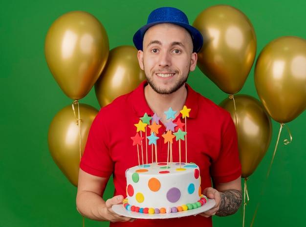 녹색 배경에 고립 된 카메라를보고 생일 케이크를 들고 풍선 앞에 서있는 파티 모자를 쓰고 웃는 젊은 잘 생긴 슬라브 파티 남자