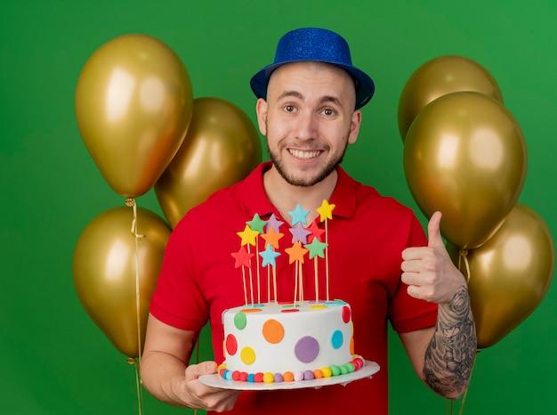 녹색 배경에 고립 된 카메라를보고 엄지 손가락을 보여주는 생일 케이크를 들고 풍선 앞에 서있는 파티 모자를 쓰고 웃는 젊은 잘 생긴 슬라브 파티 남자