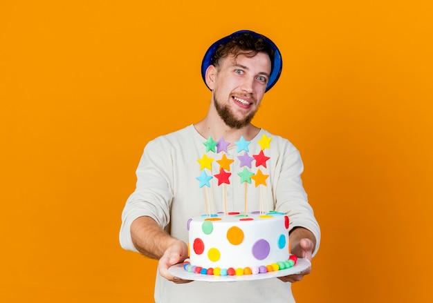 별과 생일 케이크를 뻗어 복사 공간이 오렌지 배경에 고립 된 카메라를보고 파티 모자를 쓰고 젊은 잘 생긴 슬라브 파티 남자 미소