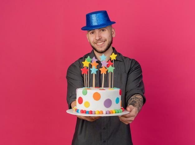 복사 공간이 진홍색 배경에 고립 된 카메라를보고 카메라를 향해 별 생일 케이크를 뻗어 파티 모자를 쓰고 웃는 젊은 잘 생긴 슬라브 파티 남자