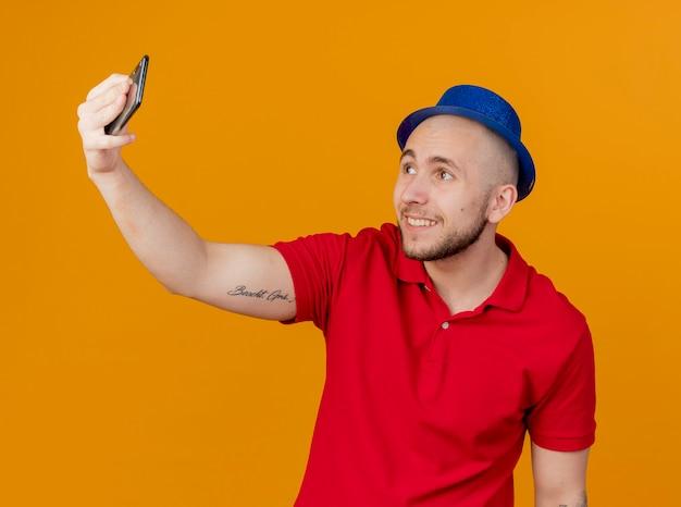 オレンジ色の背景で隔離のselfieを取るパーティー帽子をかぶって若いハンサムなスラブパーティー男を笑顔