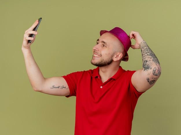 帽子に触れて、オリーブグリーンの背景で隔離のselfieを取るパーティーハットを身に着けている若いハンサムなスラブパーティー男を笑顔