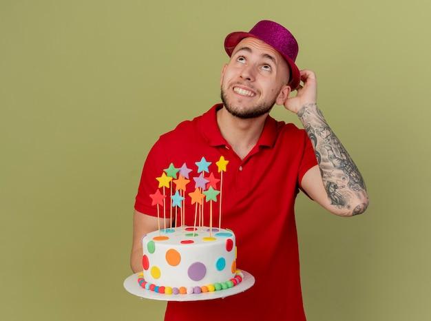 コピースペースでオリーブグリーンの背景に分離された見上げる誕生日ケーキを保持している帽子に触れるパーティーハットを身に着けている若いハンサムなスラブ党の男を笑顔