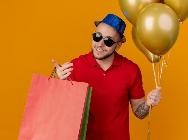 Sorridente giovane bel partito slavo ragazzo che indossa occhiali da sole e cappello da festa tenendo palloncini e sacchetti di carta che punta a lato isolato su sfondo arancione