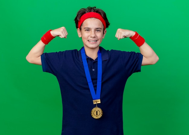 Улыбающийся молодой красивый спортивный мальчик с головной повязкой и браслетами и медалью на шее с зубными скобами, глядя вперед, делая сильный жест, изолированный на зеленой стене