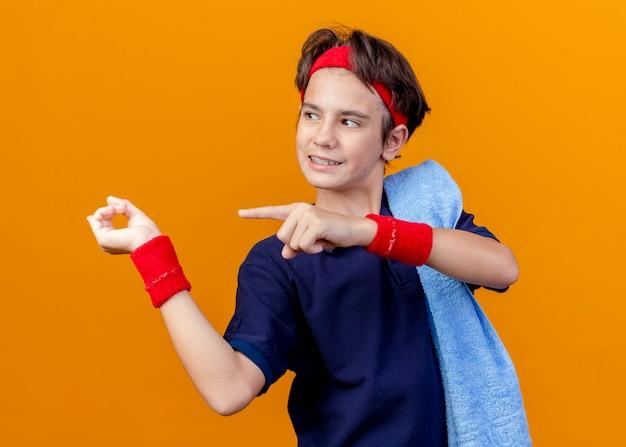 オレンジ色の背景で隔離の側を見て、肩に歯科用ブレースとタオルでヘッドバンドとリストバンドを身に着けている若いハンサムなスポーティな男の子の笑顔