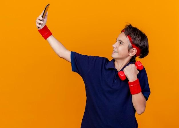 オレンジ色の背景で隔離のselfieを取るダンベルを保持している歯科用ブレースとヘッドバンドとリストバンドを身に着けている若いハンサムなスポーティな男の子の笑顔