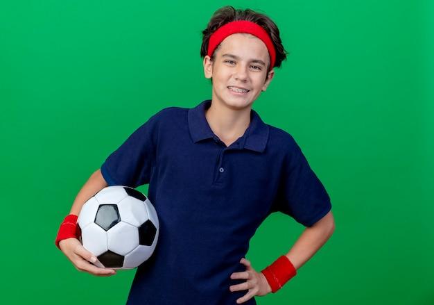 コピースペースで緑の背景に分離されたカメラを見て腰に手を保ちながらサッカーボールを保持している歯科用ブレースとヘッドバンドとリストバンドを身に着けている若いハンサムなスポーティな男の子の笑顔
