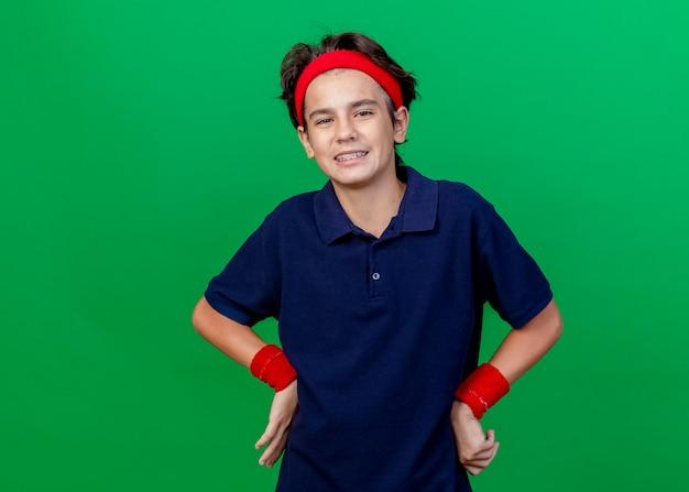 복사 공간이 녹색 배경에 고립 된 카메라를보고 허리에 손을 유지 치과 교정기와 머리띠와 팔찌를 착용하는 젊은 잘 생긴 스포티 한 소년 미소