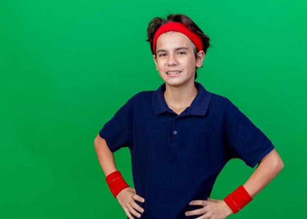 복사 공간이 녹색 벽에 고립 된 전면을보고 허리에 손을 유지 치과 교정기와 머리띠와 팔찌를 착용하는 젊은 잘 생긴 스포티 한 소년 미소