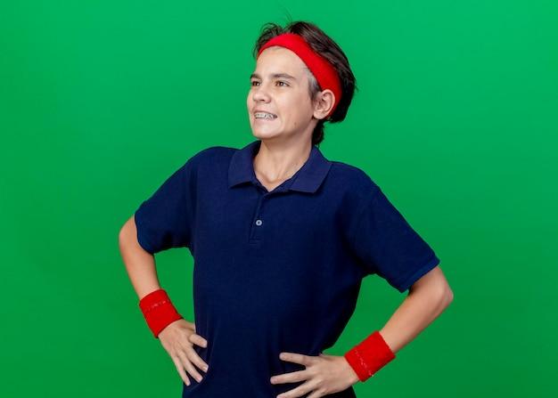 コピースペースのある緑の壁に孤立してまっすぐに見える腰に手を保ちながら、ヘッドバンドとリストバンドを身に着けている若いハンサムなスポーティな男の子の笑顔