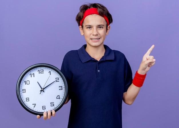紫色の背景で隔離の側を指している時計を保持しているカメラを見て歯科ブレースとヘッドバンドとリストバンドを身に着けている若いハンサムなスポーティな少年の笑顔