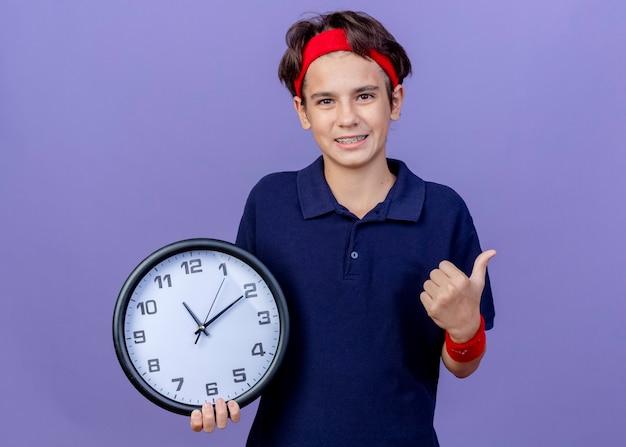 コピースペースで紫色の背景に分離された親指を示す時計を保持しているカメラを見て歯科ブレースとヘッドバンドとリストバンドを身に着けている若いハンサムなスポーティな少年の笑顔