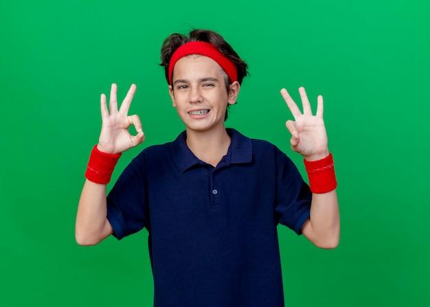 Улыбающийся молодой красивый спортивный мальчик, носящий повязку на голову и браслеты с зубными скобами, глядя вперед, делает хорошо, знак изолирован на зеленой стене