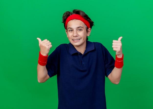 ヘッドバンドとリストバンドを身に着けている若いハンサムなスポーティな少年の笑顔は、コピースペースで緑の壁に分離された親指を見せて正面を見て歯科ブレース
