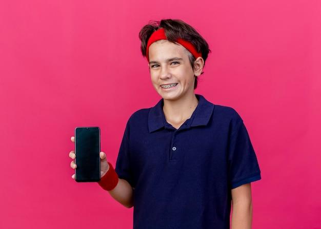 분홍색 벽에 고립 된 전면을보고 휴대 전화를 보여주는 치과 교정기와 머리띠와 팔찌를 착용하는 젊은 잘 생긴 스포티 한 소년 미소