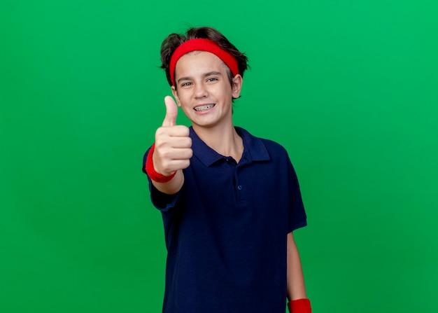 コピースペースと緑の壁に分離された親指を示す歯のブレースとヘッドバンドとリストバンドを身に着けている若いハンサムなスポーティな少年の笑顔