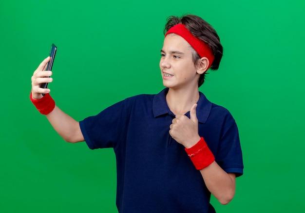 녹색 벽에 고립 된 엄지 손가락을 보여주는 셀카를 복용 치과 교정기와 머리띠와 팔찌를 착용하는 젊은 잘 생긴 스포티 한 소년 미소