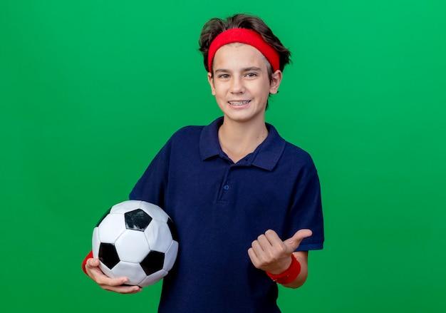 Sorridente giovane ragazzo sportivo bello che indossa la fascia e braccialetti con bretelle dentali che tiene il pallone da calcio che mostra pollice in su che guarda l'obbiettivo isolato su priorità bassa verde con lo spazio della copia