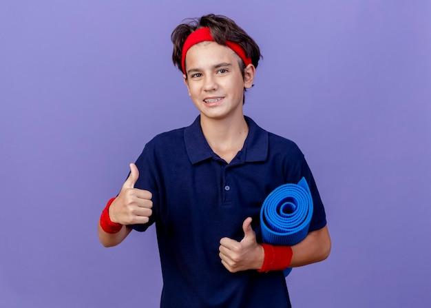 Sorridente giovane ragazzo sportivo bello che indossa la fascia e braccialetti con bretelle dentali che tiene la stuoia di yoga che mostra i pollici in su isolato sulla parete viola con lo spazio della copia