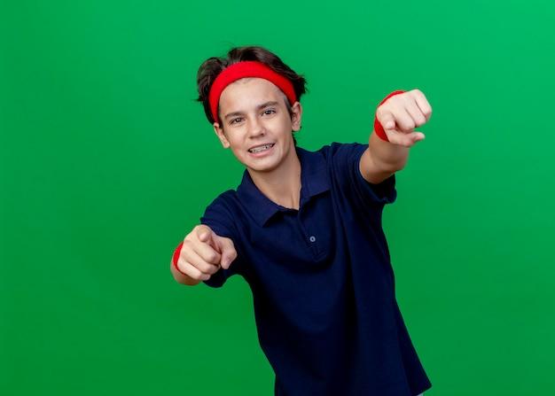 Sorridente giovane ragazzo sportivo bello che indossa la fascia e braccialetti con bretelle dentali che guarda l'obbiettivo che ti fa gesto isolato su priorità bassa verde con lo spazio della copia