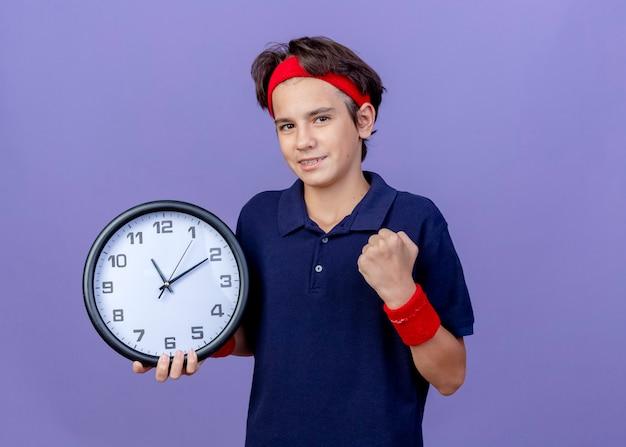 Sorridente giovane ragazzo sportivo bello che indossa la fascia e braccialetti con bretelle dentali che guarda l'obbiettivo che tiene il pugno di serraggio dell'orologio isolato su priorità bassa viola con lo spazio della copia