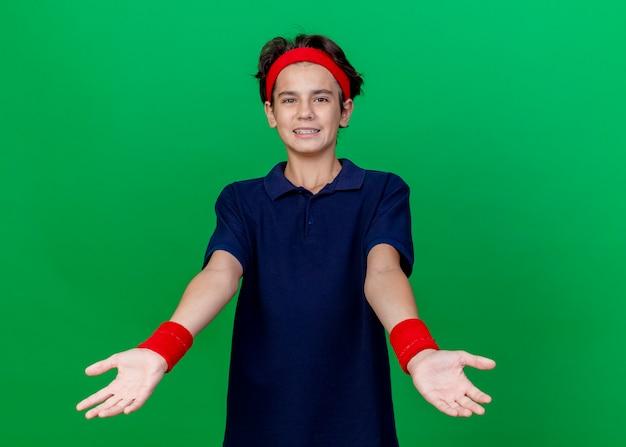 Sorridente giovane ragazzo sportivo bello che indossa la fascia e braccialetti con bretelle dentali che guarda l'obbiettivo allungando le mani verso la macchina fotografica isolata su priorità bassa verde con lo spazio della copia