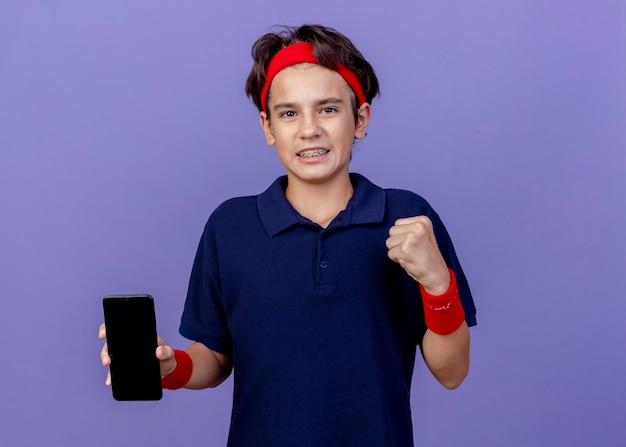 Sorridente giovane ragazzo sportivo bello che indossa la fascia e braccialetti con le parentesi graffe dentali che mostra il telefono cellulare facendo sì gesto isolato sulla parete viola con lo spazio della copia