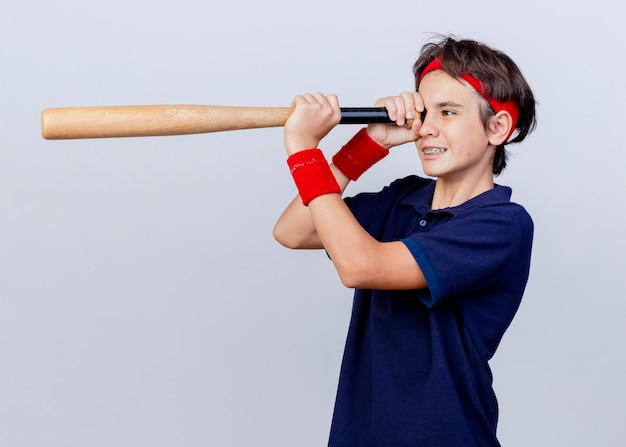 Smiling young handsome sporty boy wearing headband and wristbands with dental braces standing in profile view holding baseball bat using it as telescope isolated on white background