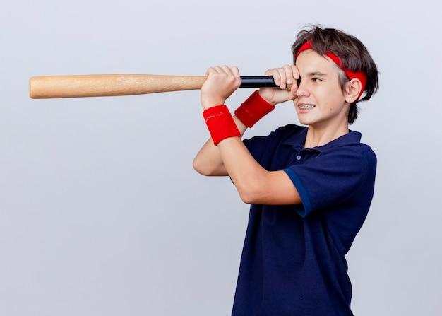 Sorridente giovane ragazzo sportivo bello che indossa fascia e braccialetti con bretelle dentali in piedi in vista di profilo tenendo la mazza da baseball usandolo come telescopio isolato su priorità bassa bianca