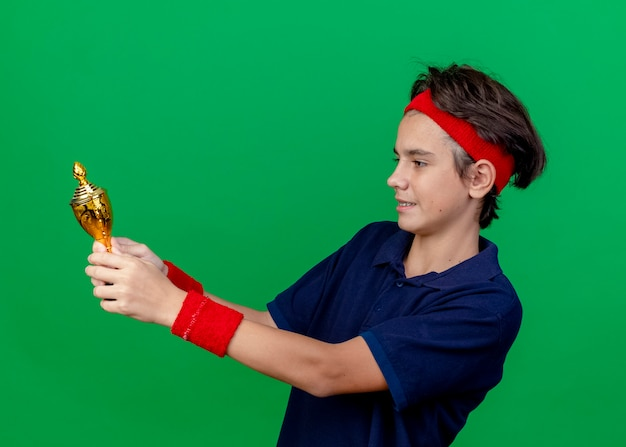 Smiling young handsome sporty boy wearing headband and wristbands with dental braces standing in profile view holding and looking at winner cup isolated on green wall