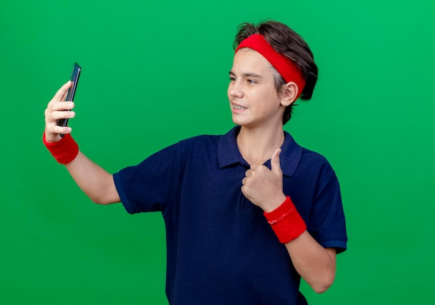 Sorridente giovane ragazzo sportivo bello che indossa la fascia e braccialetti con bretelle dentali prendendo selfie che mostra il pollice in alto isolato sulla parete verde