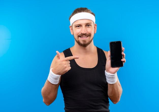 Улыбающийся молодой красивый спортивный мужчина с головной повязкой и браслетами, держащий и указывающий на мобильный телефон, изолированный на синем пространстве