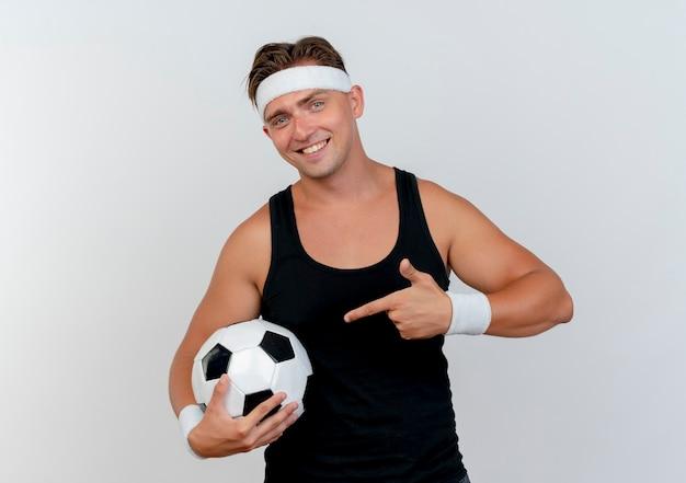 Улыбающийся молодой красивый спортивный мужчина с головной повязкой и браслетами держит и указывает на футбольный мяч, изолированный на белой стене