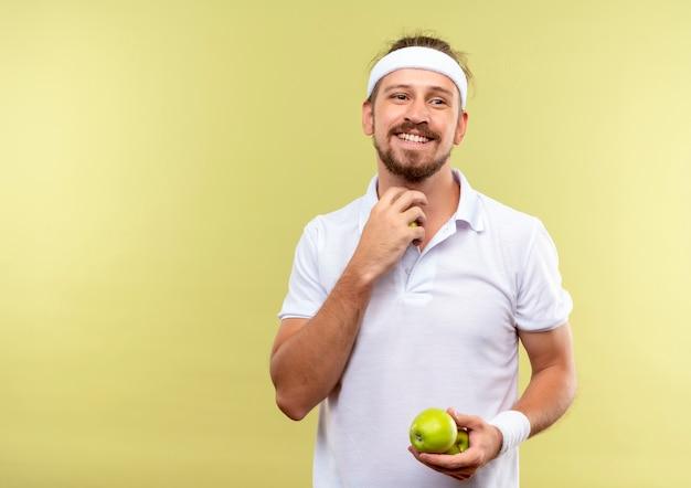 緑の空間で隔離された側を見てリンゴを保持しているヘッドバンドとリストバンドを身に着けている若いハンサムなスポーティな男の笑顔