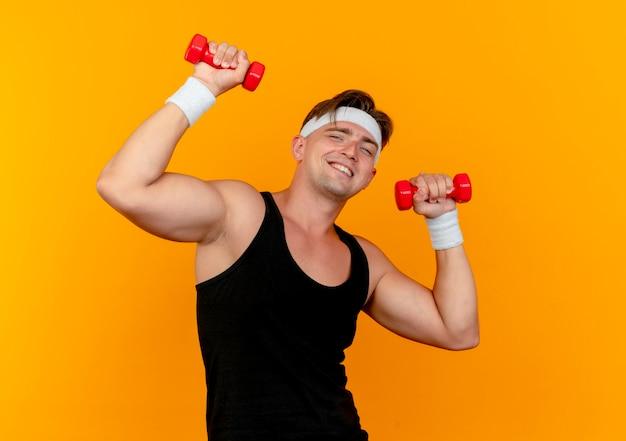 Улыбающийся молодой красивый спортивный мужчина с повязкой на голову и браслетами с гантелями, изолированными на оранжевой стене Бесплатные Фотографии