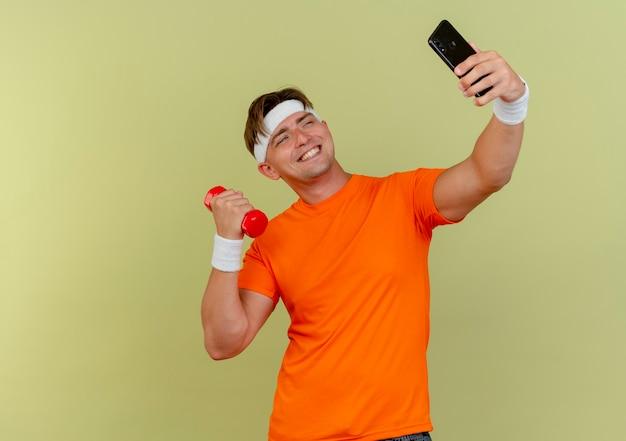 Улыбающийся молодой красивый спортивный мужчина с головной повязкой и браслетами, держащий мобильный телефон и гантель, делающий селфи на оливково-зеленой стене