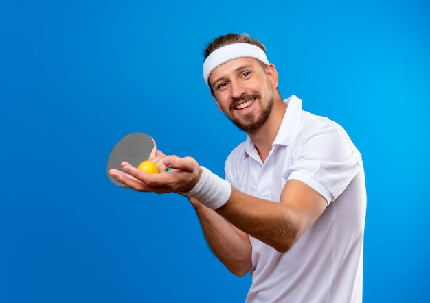 青いスペースで隔離のボールとピンポンラケットを保持しているヘッドバンドとリストバンドを身に着けている若いハンサムなスポーティな男の笑顔