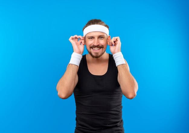 푸른 공간에 고립 된 큰 귀를 만드는 머리띠와 팔찌를 착용하는 젊은 잘 생긴 스포티 한 남자를 웃고