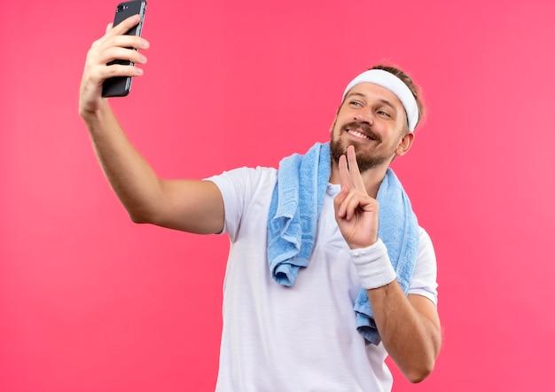 Sorridente giovane uomo sportivo bello che indossa la fascia e braccialetti facendo segno di pace prendendo selfie con asciugamano intorno al collo isolato su spazio rosa