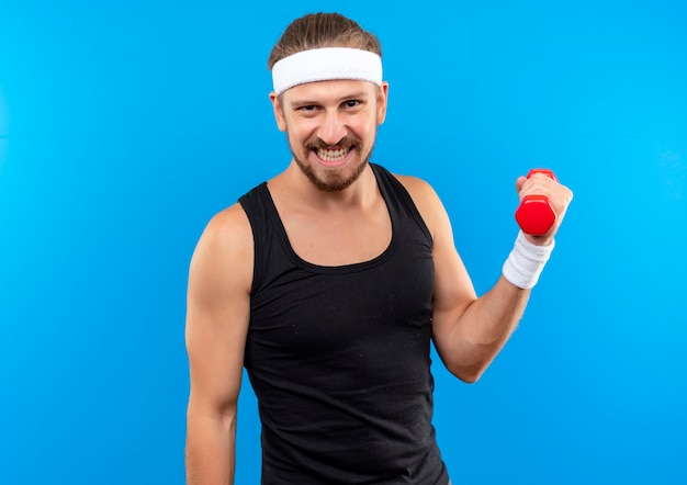 Smiling young handsome sporty man wearing headband and wristbands holding dumbbell isolated on blue space