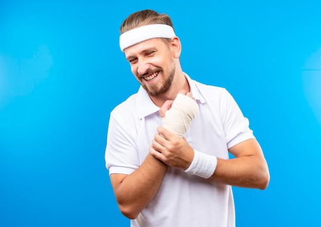 Sorridente giovane uomo sportivo bello che indossa la fascia e braccialetti che tengono il suo polso ferito avvolto con benda isolato su spazio blu