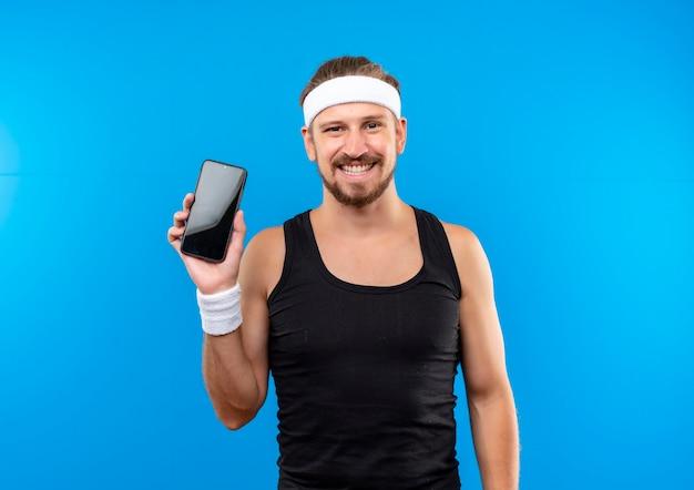 Sorridente giovane uomo sportivo bello indossando la fascia e braccialetti in possesso di telefono cellulare isolato su spazio blu