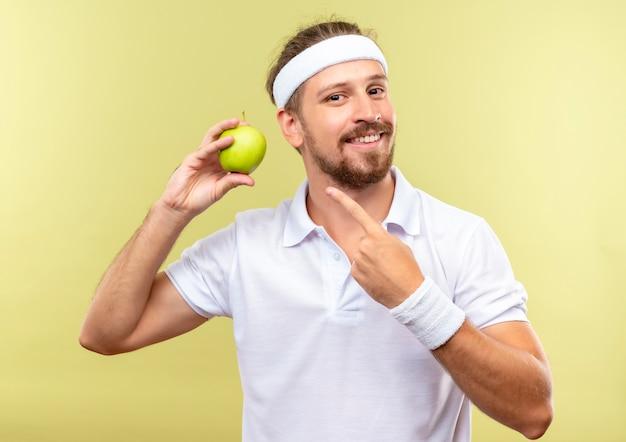 Sorridente giovane uomo sportivo bello indossando la fascia e braccialetti che tengono e che indica alla mela isolata su spazio verde