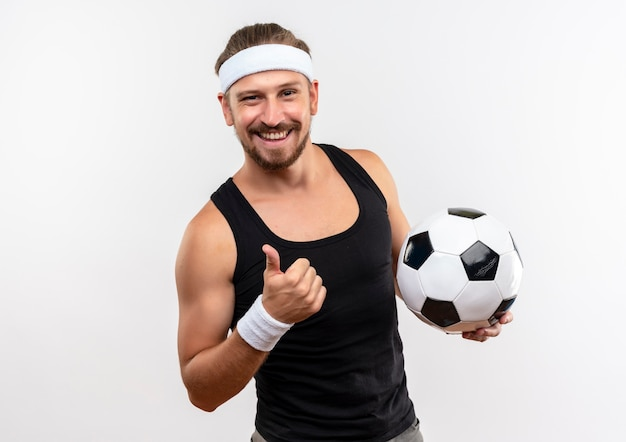 Sorridente giovane uomo sportivo bello indossando la fascia e braccialetti in possesso di pallone da calcio e mostrando il pollice in alto isolato su uno spazio bianco