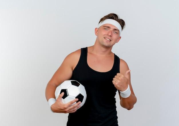 Sorridente giovane uomo sportivo bello indossando la fascia e braccialetti in possesso di pallone da calcio e mostrando il pollice in alto isolato sul muro bianco